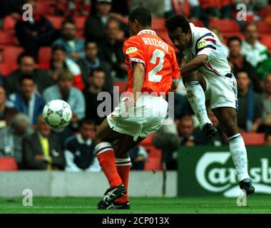 France's Patrice Loko (R) kicks the ball in front of Michael Reiziger (L) of Holland during their Euro '96 Championship at Anfield stadium on June 22. France defeated the Netherlands 5-4 in a penalty shoot-out.  SPORT SOCCER