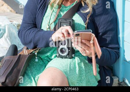 A woman uses her digital phone with a retro vintage Rolleiflex twin lens reflex camera around her neck - Stock Photo