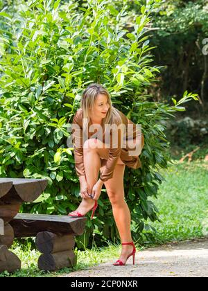 Stiletto heels legs young woman buckling buckle tying Red high-heels tie laces standing in park raising leg on wooden bench noticing somebody - Stock Photo