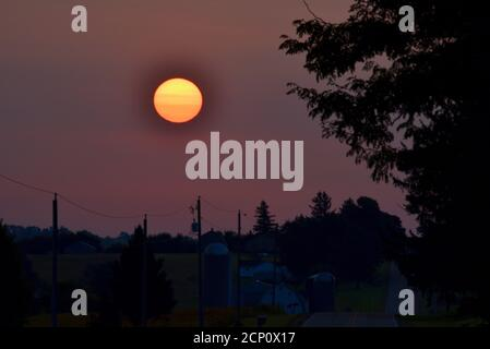 Hazy, smoke-filled sky from California and Oregon wildfires, with surreal, setting sun (no clouds) over rural countryside, Browntown, Wisconsin, USA - Stock Photo