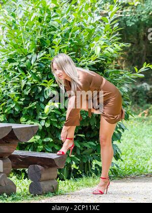 Young woman legs heels buckling buckle tying Red high-heels tie laces standing in park raising leg on wooden bench eyeshot eyes eye contact Stock Photo