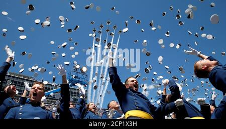 The Thunderbirds perform a fly-over as graduates from the Air Force Academy toss their hats in the air at the conclusion of their commencement ceremony in Colorado Springs, Colorado, U.S., June 2, 2016. REUTERS/Kevin Lamarque - Stock Photo