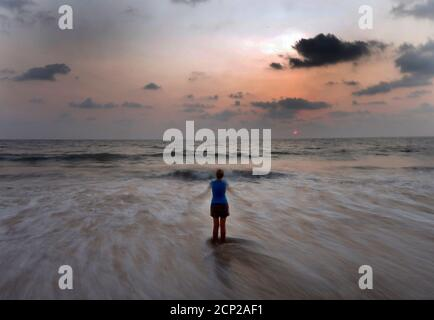 A woman performs physical exercises on a beach in Colombo March 30 ,2014. REUTERS/Dinuka Liyanawatte (SRI LANKA - Tags: SOCIETY) - Stock Photo