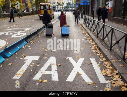 People walk down a taxi lane during a strike by taxi drivers to protest what they say is unfair competition from new car sharing companies such as Uber and Cabify, in Madrid, Spain, November 29, 2017.  REUTERS/Sergio Perez - Stock Photo