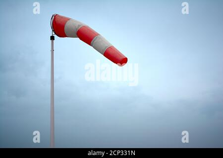 detail of a red and white wind sleeve waved in the air - Stock Photo