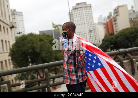 A protester wearing a protective face mask carries a U.S. flag during a demonstration in support of Brazil's President Jair Bolsonaro in Sao Paulo, Brazil, June 14, 2020. REUTERS/Amanda Perobelli - Stock Photo