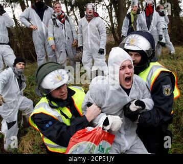 German police officers arrest an anti-nuclear protester who tried to remove stones from the railway tracks near Lemgrabe, November 26, 2011. The Castor (Cask for Storage and Transport Of Radioactive material) train is carrying 11 containers of spent German nuclear fuel on route from France after being reprocessed, to the nuclear waste storage facility of Gorleben in north eastern Germany this weekend. REUTERS/Fabrizio Bensch (GERMANY CONFLICT - Tags: POLITICS CIVIL UNREST ENVIRONMENT) CONFLICT - Stock Photo