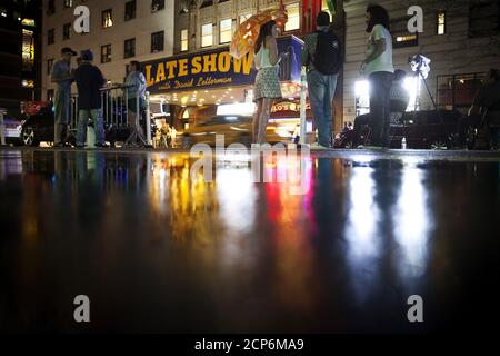 People stand and wait for a sign crew to remove the marquee across the street from the Ed Sullivan Theater where 'The Late Show' with David Letterman used to tape in the Manhattan borough New York May 27, 2015. The taping and broadcast of the final edition of 'The Late Show' was May 20, and workers are now slowly transforming the theater for the show's new host Stephen Colbert which will premiere on September 8, 2015.   REUTERS/Carlo Allegri