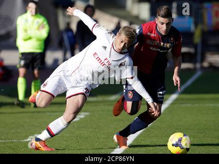 AC Milan's Keisuke Honda (L) of Japan challenges Nicola Murro of Cagliari during their Italian Serie A soccer match at the Sant'Elia stadium in Cagliari January 26, 2014. REUTERS/MAx Rossi(ITALY - Tags: SPORT SOCCER) - Stock Photo