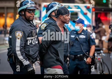A protestor is arrested by NYPD offiicers during a demonstration against Immigration and Customs Enforcement in New York City on September 18, 20202. For a third day in a row, protestors demonstrated against alleged accusations that a physician perfomed medically unnecessary hysterectomies on undocumented women in I.C.E. custody. (Photo by Gabriele Holtermann/Sipa USA) Credit: Sipa USA/Alamy Live News - Stock Photo