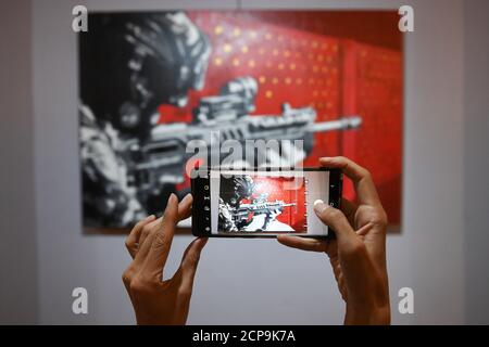 A woman takes photo of a painting by a graffiti artist Headache Stencil during his exhibition at The Foreign Correspondents' Club of Thailand (FCCT) in Bangkok, Thailand, July 31, 2020. Picture taken July 31, 2020. REUTERS/Chalinee Thirasupa - Stock Photo