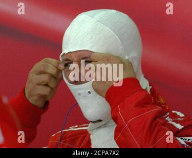 FERRARI FORMULA ONE DRIVER MICHAEL SCHUMACHER OF GERMANY PUTS ON BALACLAVA DURING THE FREE PRACTICES IN SAKHIR.  Ferrari Formula One world champion Michael Schumacher of Germany adjusts his balaclava during the free practice of the inaugural Formula One Grand Prix i Sakhir, April 2, 2004. Michael Schumacher set a red hot pace in the shimmering heat when Formula One drivers got to grips with Bahrain's desert circuit for the first time on Friday. REUTERS/Stefano Rellandini - Stock Photo