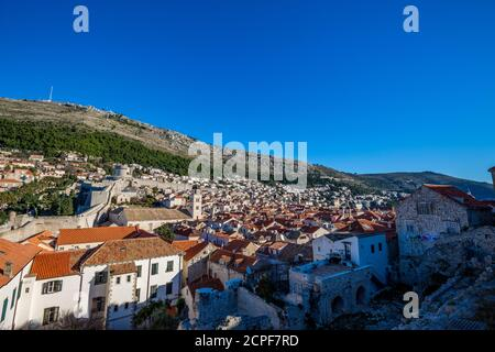 Colorful fortress street walk scene, clear sky sunny day. Beautiful building roofs. Scenery winter view of Mediterranean old city of Dubrovnik, famous European travel and historic destination, Croatia - Stock Photo