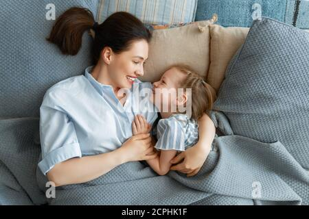A nice girl and her mother enjoy sunny morning. Good time at home. Child waking up from sleep. Family playing on the bed in the bedroom.