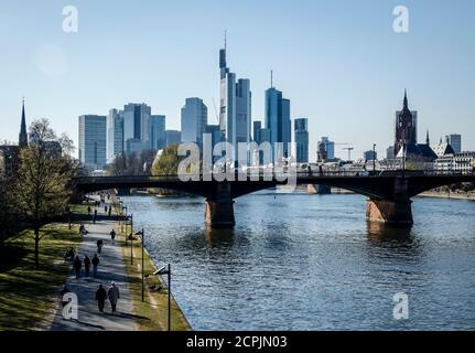 People walk on the banks of the Main in front of the skyline of downtown Frankfurt with the banking district, Frankfurt am Main, Hesse, Germany - Stock Photo