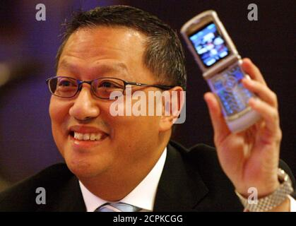 Simon Leung, Motorola Senior Vice President and General Manager of Motorola Asia Pacific Limited, shows a new mobile phone model V3 during the Reuters Asia Technology Summit in Shanghai September 20, 2004. U.S. telecoms gear maker Motorola Inc. said on Monday it is testing equipment for a new Chinese mobile phone standard, joining rivals scrambling to prepare for multi-million dollar contracts after years of scepticism over the technology. REUTERS/Claro Cortes IV  CC/CP - Stock Photo
