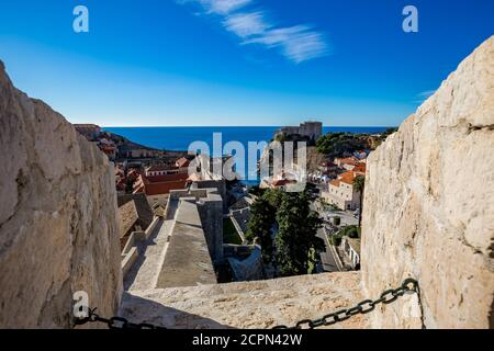 Colorful fortress street walk scene, clear sky sunny day. Beautiful high angle scene. Winter view of Mediterranean old city of Dubrovnik, famous European travel and historic destination, Croatia - Stock Photo