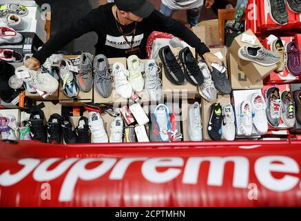 A seller shows his sneakers to visitors at the KICKIT Sneaker e Streetwear Market in Rome, Italy, September 23, 2018. Picture taken September 23, 2018. REUTERS/Alessandro Bianchi - Stock Photo