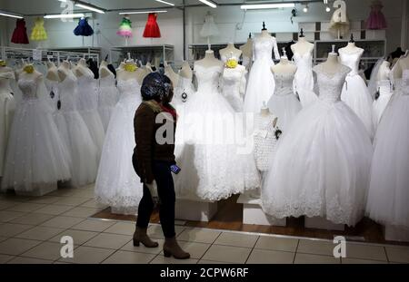 A customer walks past wedding dresses at a bridal shop ih Johannesburg, South Africa May 14, 2018. REUTERS/Siphiwe Sibeko Stock Photo