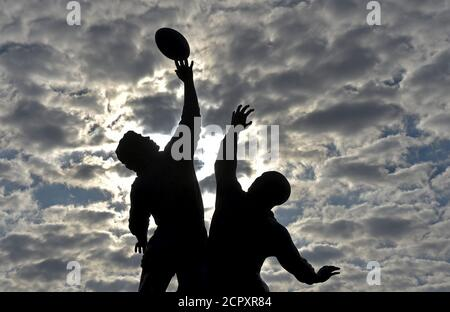 The sun rises behind a statue of rugby players reaching for the ball, outside Twickenham rugby stadium in west London September 17, 2015. The eight metre bronze sculpture was created by artist Gerald Laing in 2010. The Rugby Union World Cup begins in Britain tomorrow, with both the opening game and ceremony and final taking place at Twickenham.  REUTERS/Toby Melville