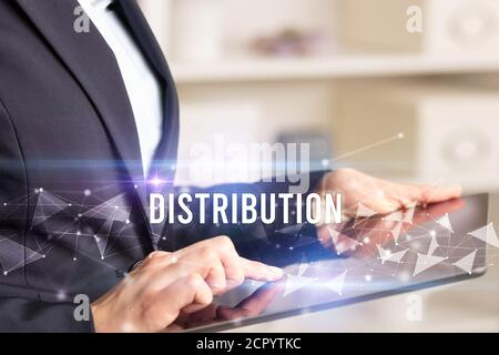Close up hands using tablet with DISTRIBUTION inscription, modern business technology concept