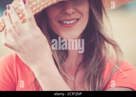 Close up woman portrait in vintage pink tones with cheerful and happy hidden eyes young caucasian lady with long beautiful hair and hat - concept of