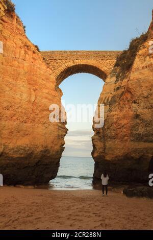 Praia dos Estudantes beach during Sunset with arch bridge in Lagos, Algarve, Portugal