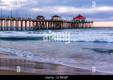 Seascape of the Huntington Beach pier at sunset, with slow shutter speed. Ruby's Diner is located at the end of the pier and is popular with tourists. - Stock Photo