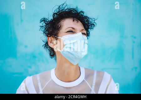 Close up of mature woman with curly short hair wearing safety mask against blue wall