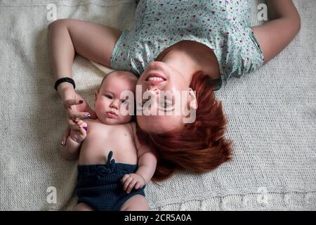 close-up portrait of mom and baby lying on the floor Stock Photo