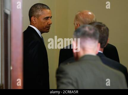 U.S. President Barack Obama (L) departs the White House Roosevelt Room after announcing plans to slow the withdrawal of U.S. troops from Afghanistan, after delivering a statement in Washington October 15, 2015. The plan would keep the current force of 9,800 through most of 2016 before beginning to trim levels. Vice President Joe Biden, Secretary of Defense Ash Carter and Chairman of the Joint Chiefs of Staff Joseph Dunford joined the president for the announcement. REUTERS/Jonathan Ernst - Stock Photo