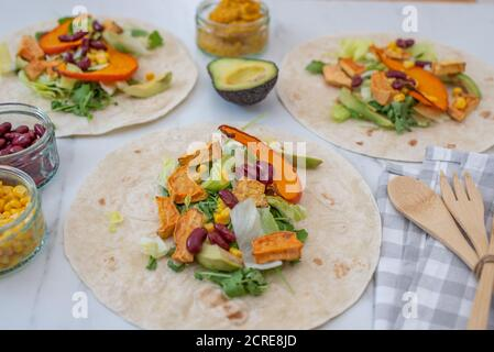 Open vegan tortilla wraps with sweet potato, beans, avocado and pumpkin - Stock Photo