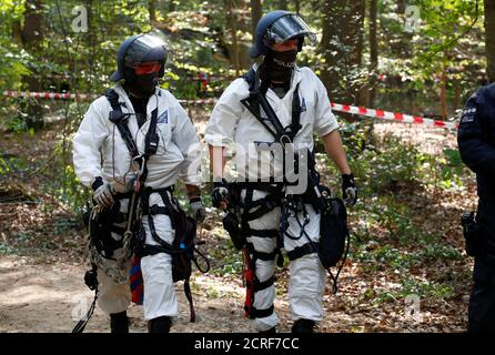 Two special police forces, the one at right equipped with a high-precision paint-ball gun, walk through the forest 'Hambacher Forst' in Kerpen-Buir near Cologne, Germany, September 14, 2018, where protesters have built a camp with tents and treehouses to stop the clearing of the Hambach forest for a nearby open cast coal mining. REUTERS/Wolfgang Rattay - Stock Photo