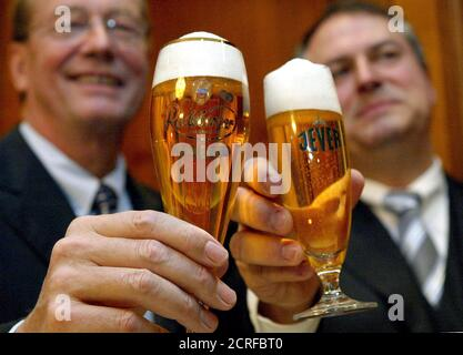 Ulrich Kallmeyer, general adviser to German family-owned food giant Dr Oetker food group and Radeberger brewery (L) and Michael Hollmann, CEO of brewer Brau and Brunnen AG toast with their company's beers after they announced the merger of Brau and Brunnen with the Oetker group during a news conference in Frankfurt February 13, 2004. REUTERS/Kai Pfaffenbach  KP/JOH/JV - Stock Photo