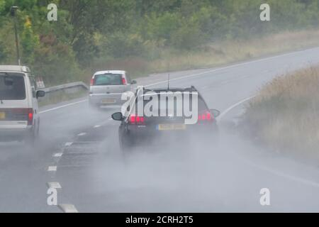 Drivers driving cars on a Dual Carriageway during heavy rain with poor visibility in England, UK. Bad weather and wet, dangerous road while raining. - Stock Photo
