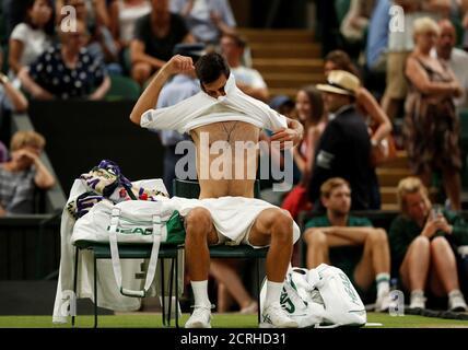 Tennis - Wimbledon - All England Lawn Tennis and Croquet Club, London, Britain - July 13, 2018  Serbia's Novak Djokovic changes his shirt during his semi final match against Spain's Rafael Nadal   REUTERS/Andrew Boyers - Stock Photo