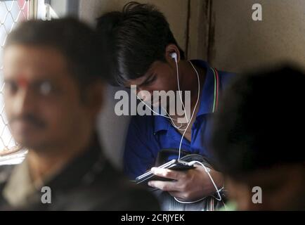 A man watches a video on his mobile phone as he commutes by a suburban train in Mumbai, India, March 31, 2016. With smartphone sales booming and India preparing for nationwide 4G Internet access, India's film and TV industry hopes the ease of tapping your phone for the latest release will generate profits at last, overcoming the problems of woefully few cinemas and rampant piracy. Picture taken March 31, 2016. REUTERS/Shailesh Andrade