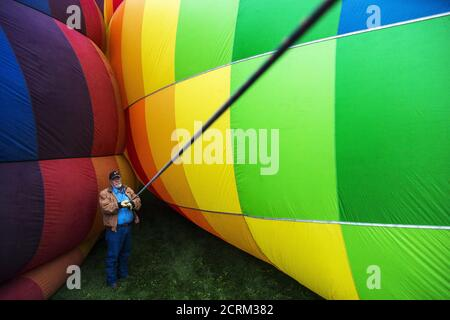 A man holds a guide line as he stands between two hot air balloons being prepared for lift off on the first day of the 2015 Albuquerque International Balloon Fiesta in Albuquerque, New Mexico, October 3, 2015.  REUTERS/Lucas Jackson - Stock Photo