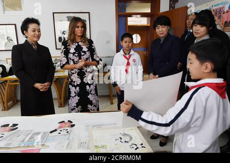 U.S. First Lady Melania Trump (2nd L) and China's First Lady Peng Liyuan (L) are shown an art work in a calligraphy class during a visit to Banchang Primary School in Beijing on November 9, 2017.   REUTERS/ Greg Baker/Pool - Stock Photo