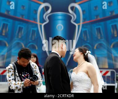 A photographer takes a picture of a newly married couple in front of the UEFA Champions League Final 2016 banner in Duomo's square downtown Milan, Italy, May 23, 2016. REUTERS/Stefano Rellandini