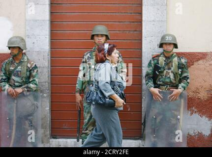 A woman walks past soldiers standing guard down centre in Tegucigalpa July 7, 2009. U.S. Secretary of State Hillary Clinton on Tuesday said Costa Rican President Oscar Arias should lead talks between Zelaya and those who led the June 28 coup. REUTERS/Henry Romero (HONDURAS POLITICS CONFLICT) Stock Photo