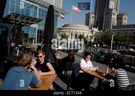 People sit at a Hard Rock Cafe in front of the Palace of Culture and Science in centre of Warsaw, Poland September 21, 2018. Picture taken September 21, 2018. REUTERS/Kacper Pempel - Stock Photo