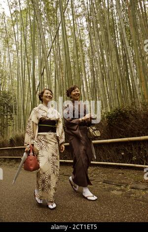 Japanese women wearing traditional kimono and walking along the Sagano Bamboo Forest in Arashiyama, Kyoto, Japan 2012