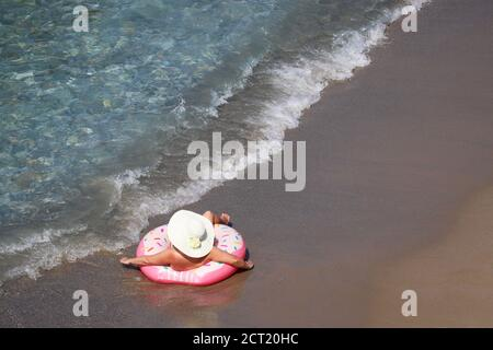 Woman in hat laying on inflatable donut ring on a sand in sea waves, aerial view. Beach vacation, relax and leisure in clean water