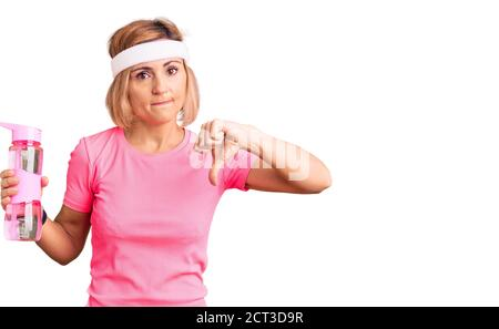 Young blonde woman wearing sportswear holding water bottle with angry face, negative sign showing dislike with thumbs down, rejection concept - Stock Photo