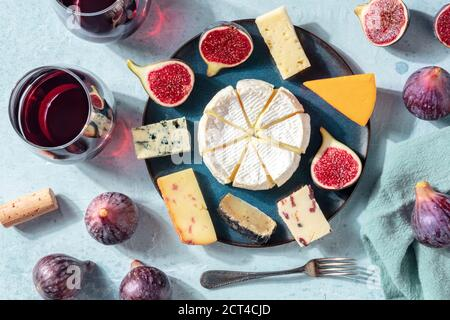 Cheese variety, wine and figs, flat lay, overhead shot on a blue background - Stock Photo