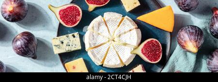 Cheeses panorama, a flat lay with figs, shot from above on a blue background - Stock Photo