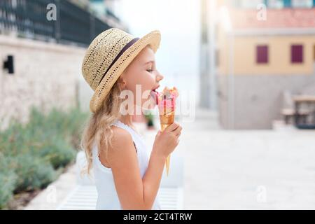 Kid is eating ice cream. Little girl is enjoying melting italian gelato.
