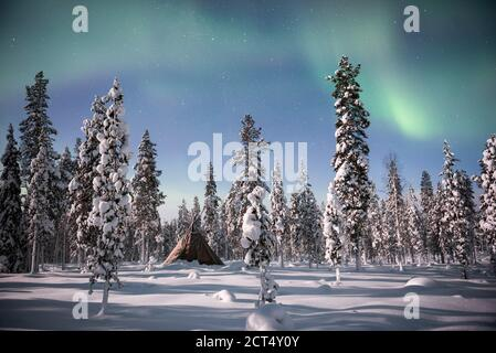 Northern Lights (aurora borealis) above a tent teepee kota in the forest in winter in Finnish Lapland, inside Arctic Circle in Finland - Stock Photo