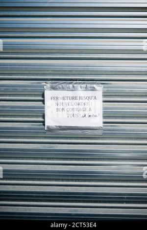 a printed sign in french with handwritten correction stuck on closed metal shutter of shop saying closed until further notice, all the best everyone! - Stock Photo